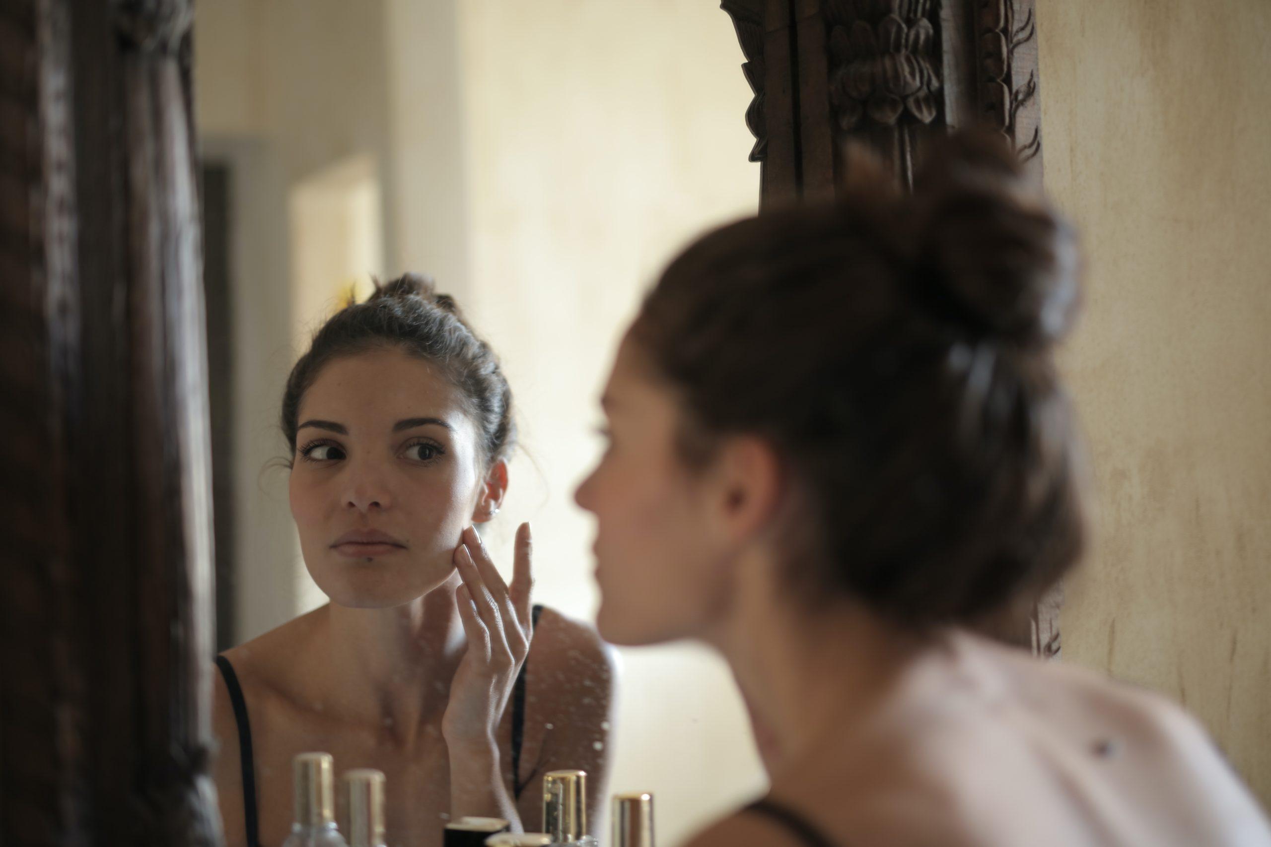 Mulher cuidando da pele em frente ao espelho autocuidado
