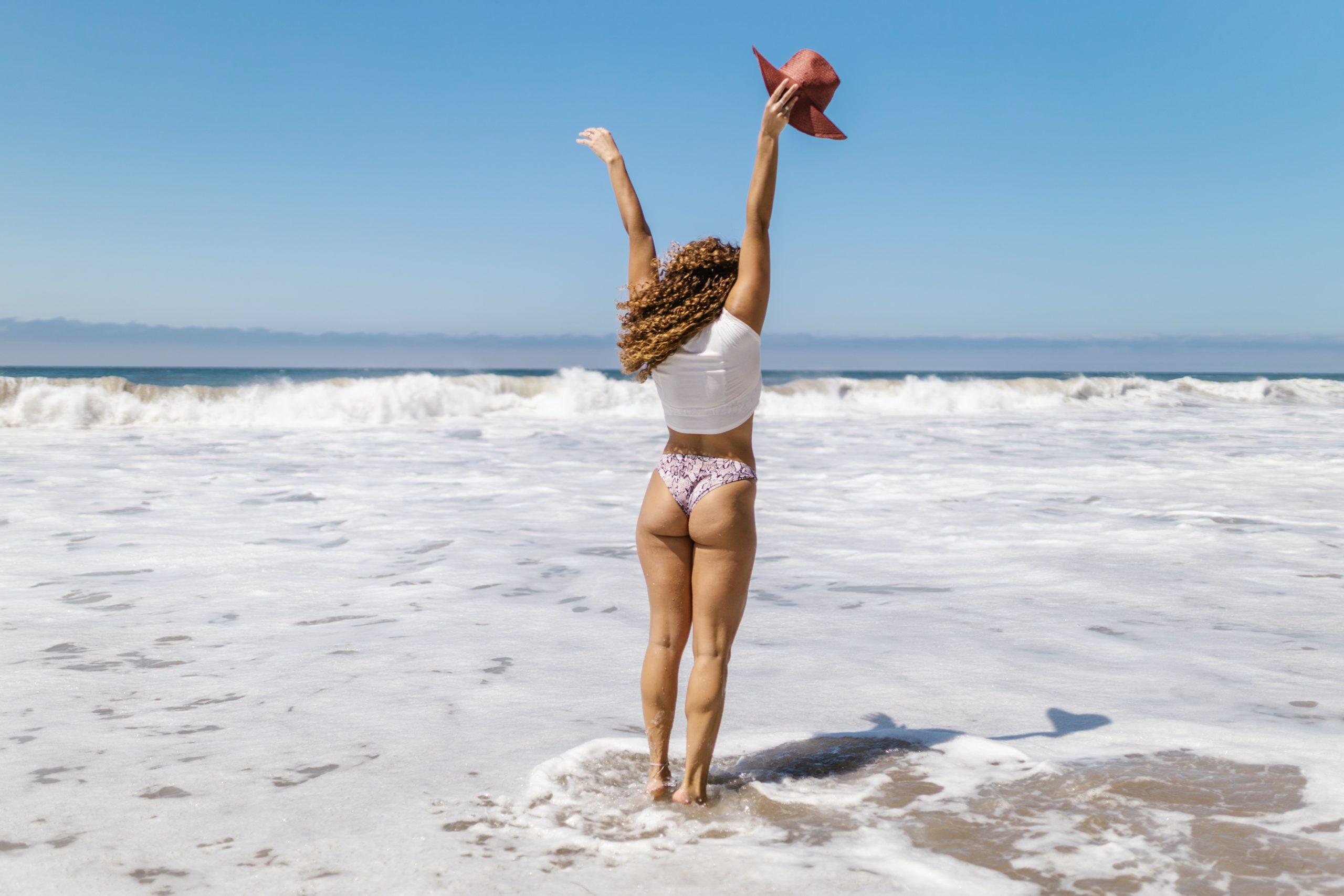Mulher de biquíni na praia durante o verão. Acelerar o metabolismo